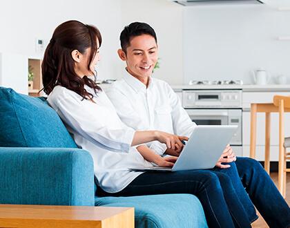 自宅でPCを見ている夫婦イメージ